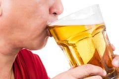喝一个大杯子刷新的成熟的人冰镇啤酒 免版税库存图片