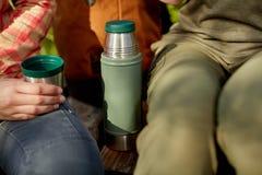 喝一个杯子从烧瓶的咖啡的妇女 免版税库存图片