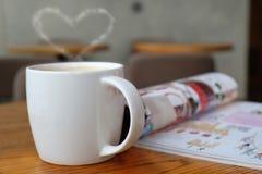 喝一个杯子热的咖啡,当读书时 免版税图库摄影