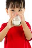 喝一个杯子牛奶的亚裔矮小的中国女孩 免版税库存照片