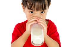 喝一个杯子牛奶的亚裔矮小的中国女孩 免版税图库摄影