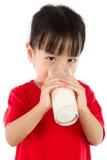 喝一个杯子牛奶的亚裔矮小的中国女孩 库存照片
