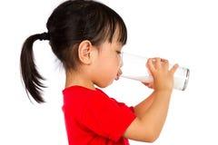 喝一个杯子牛奶的亚裔矮小的中国女孩 图库摄影