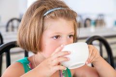 喝一个杯子牛奶的小女孩在早餐 图库摄影