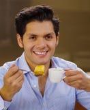 喝一个杯子coffe和吃一块可口传统土耳其食物果仁蜜酥饼的英俊的人和在棕色背景 免版税库存照片