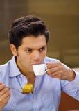 喝一个杯子coffe和吃一块可口传统土耳其食物果仁蜜酥饼的英俊的人和在棕色背景 库存照片