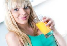 喝一个桔子的可爱的女孩在厨房里 库存图片