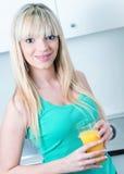 喝一个桔子的可爱的女孩在厨房里 库存照片