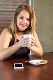 喝一个热的饮料的可爱的妇女 免版税库存照片