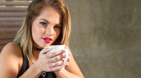 喝一个热的饮料的可爱的妇女 免版税图库摄影