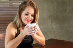 喝一个热的饮料的可爱的妇女 库存照片