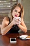 喝一个热的饮料的可爱的妇女 库存图片
