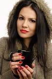 喝一个热的饮料的美丽的女孩。 免版税图库摄影