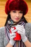喝一个热的饮料的美丽的女孩。 免版税库存图片
