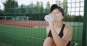 喝一个瓶水的吸引人微笑的夫人下来坐草在网球场,在开始前 股票视频