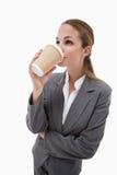 喝一份外带的咖啡的女实业家 免版税库存照片