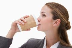 喝一份外带的咖啡的女实业家 库存图片
