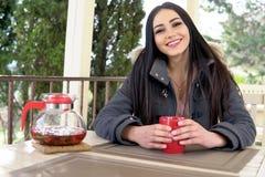 喝一份热的饮料的女孩在室外餐馆 库存照片