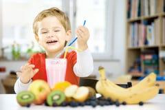 喝一名健康圆滑的人的愉快的小男孩在他的舒适家, w 图库摄影
