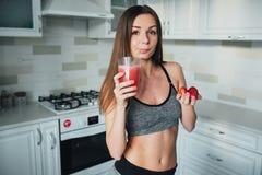 喝一名可口圆滑的人用莓果的性体育女孩 库存图片