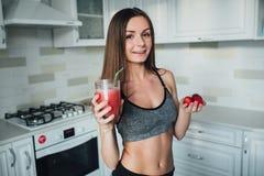 喝一名可口圆滑的人用莓果的性体育女孩 免版税库存图片