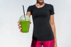 喝一名绿色圆滑的人的健康生活方式妇女 免版税库存图片