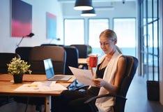 喝一杯咖啡和读busi的企业白肤金发的女孩 免版税库存照片