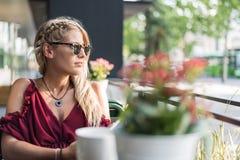 喝一杯咖啡在大阳台的美丽的白肤金发的妇女 免版税图库摄影