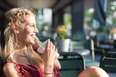 喝一杯咖啡在大阳台的美丽的白肤金发的妇女 免版税库存照片