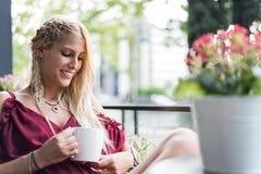 喝一杯咖啡在大阳台的美丽的白肤金发的妇女 免版税库存图片