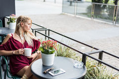 喝一杯咖啡在大阳台的美丽的白肤金发的妇女 图库摄影
