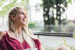 喝一杯咖啡在大阳台的美丽的白肤金发的妇女 库存照片