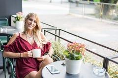 喝一杯咖啡在大阳台的美丽的白肤金发的妇女 库存图片