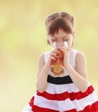 喝一杯橙汁的女孩 图库摄影