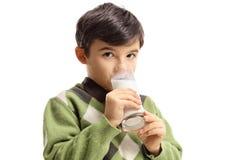喝一杯牛奶的男孩 库存照片