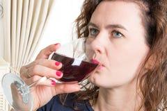 喝一杯酒的蓝眼睛妇女 免版税库存照片