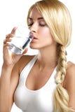 喝一杯水的年轻美丽的妇女 免版税库存照片