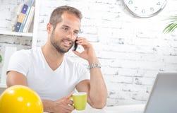 喝一份咖啡,在电话的一个年轻商人 免版税库存图片