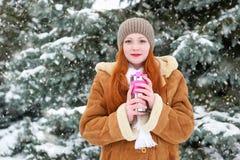 喝一份热的饮料的美丽的妇女和在森林,长的红色头发里保持温暖在室外的冬天,多雪的冷杉木,佩带sheepski 图库摄影