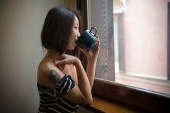 喝与蓝色杯子的美丽的亚裔妇女看窗口 免版税库存图片