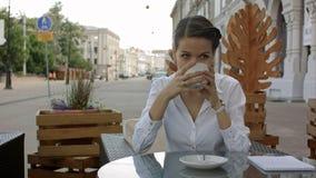 喝从一个杯子的妇女一份咖啡在餐馆大阳台,当认为和看斜向一边时 免版税库存照片