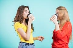 喝从一次性纸杯的两个微笑的愉快的少妇或十几岁的女孩咖啡在蓝色背景 免版税库存图片