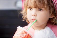 喝从与秸杆的玻璃的小孩女孩 库存照片