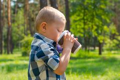 喝从塑料杯子的一个小男孩在晴朗的公园 库存图片