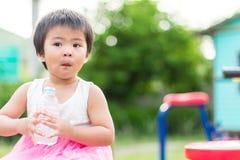 喝从塑料瓶的亚裔矮小的逗人喜爱的女孩净水 免版税库存照片