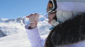 喝从塑料瓶的女子滑雪者净水在山背景 股票视频