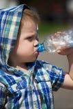 喝从塑料瓶的小男孩 免版税库存照片
