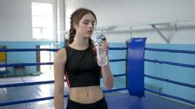喝从塑料瓶的疲倦的运动员女性矿泉水在训练期间在健身房 影视素材
