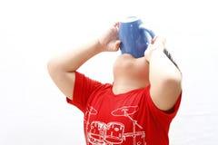 喝从杯子的小男孩 免版税库存图片