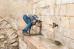 喝从水源的孩子 免版税库存照片